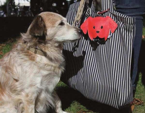 Hundekotbeutelhalter in rot befestigt an der Handtasche