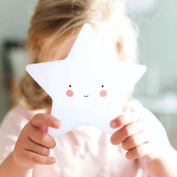 Mädchen hält mini Leuchte Stern in den Händen